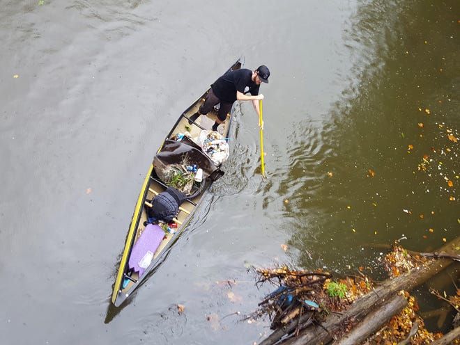 Adam Scott positions his canoe to pick up trash from a brush pile during the 2019 Mohican River cleanup.