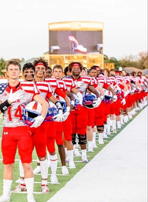 Heritage High School football players stand for the national anthem before Friday night's non-district game at Kennedale.