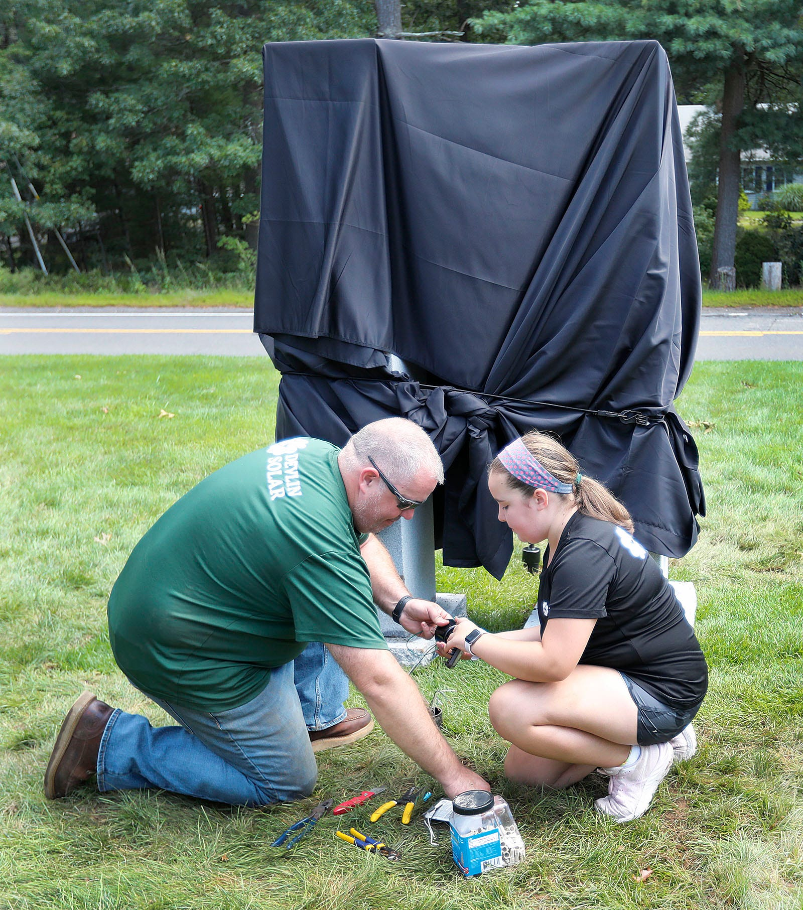 Lighting specialist Matt Devlin and daughter Megan, 12, work on a  9/11 memorial outside the Duxbury Fire Department headquarters on Tremont Street. The memorial will be unveiled Saturday, Sept. 11 at 8:20 a.m.