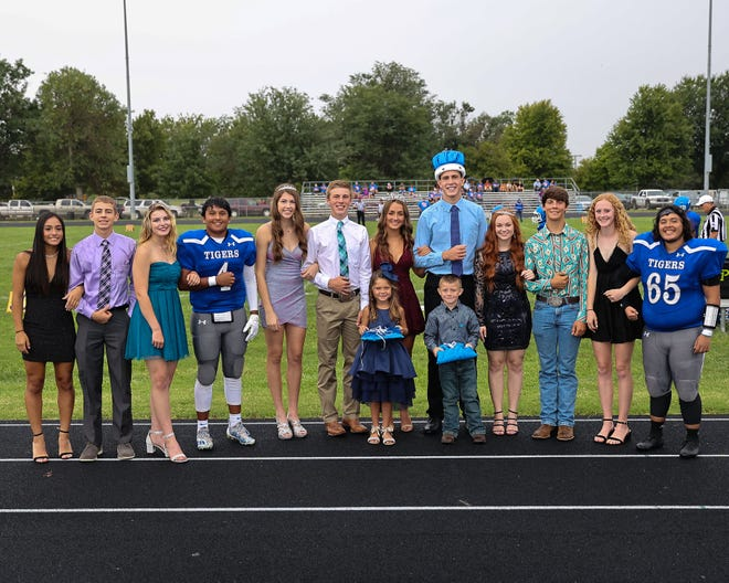 Members of the 2021 St. John-Hudson High School royal court stand in the raindrops for a group picture Friday, prior to the first home football game of the season in St. John.