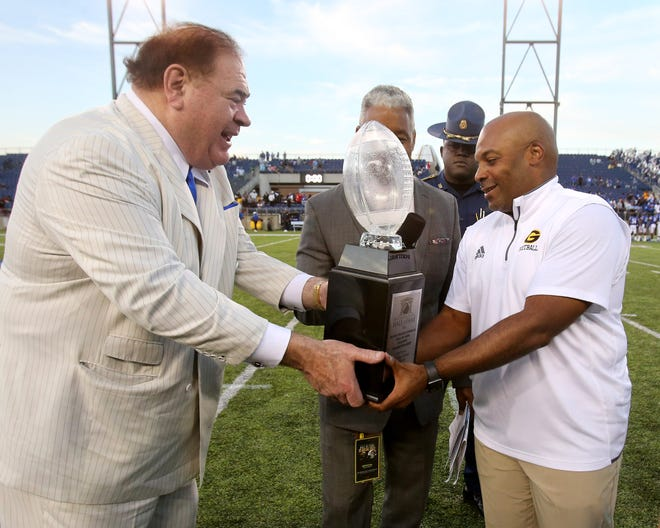 David Baker, left, president and CEO of the Pro Football Hall of Fame, presents the game trophy Sunday to Broderick Fobbs, head coach of Grambling State after the Black College Football Hall of Fame Classic against Tennessee State at Tom Benson Hall of Fame Stadium in Canton.