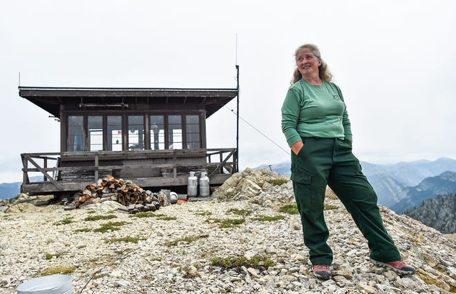 Samsara Duffey looks north from atop Patrol Mountain recently, outside the Patrol Mountain Lookout where she has spent the last 25 summers on the eastern edge of the Bob Marshall Wilderness.