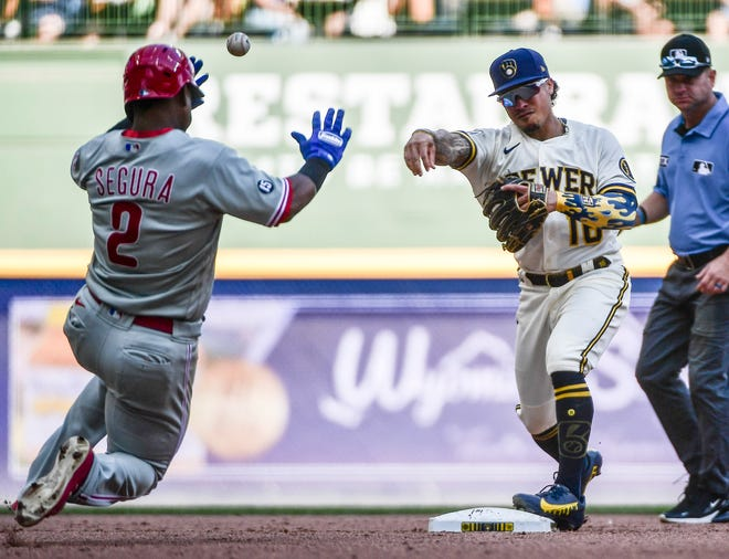 Sep 6, 2021; Milwaukee, Wisconsin, USA;  Milwaukee Brewers second baseman Kolten Wong (16) completes a double play after forcing out Philadelphia Phillies shortstop Jean Segura (2) in the seventh inning at American Family Field. Mandatory Credit: Benny Sieu-USA TODAY Sports
