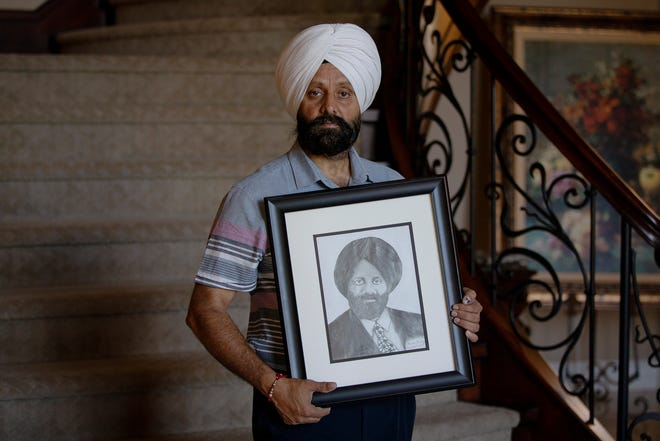 Rana Singh Sodhi stands with a hand-drawn portrait of his brother, Balbir, who was murdered days after 9/11. Singh Sodhi said the portrait was gifted to him in 2017 by a student at one of the schools he visited.