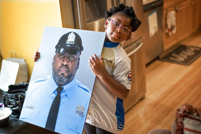 """Amethyst, Erin """"Toke"""" Tokley's five year old daughter, holds a photo of her father, on Aug. 29, 2021, in Secane, Pa. Tokley — """"Toke"""" to his friends and family — died on March 3, becoming the Philadelphia Police Department's sixth confirmed COVID-19 death. (AP Photo/Laurence Kesterson)"""