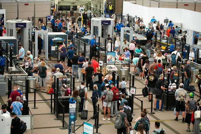 Travelers wear face coverings in the line for the north security checkpoint in the main terminal of Denver International Airport Tuesday, Aug. 24, 2021, in Denver. Two months after the Sept. 11, 2001 attacks, President George W. Bush signed legislationcreating the Transportation Security Administration,a force of federal airport screeners that replaced the private companies that airlines were hiring to handle security. (AP Photo/David Zalubowski)