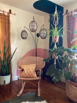 A mural arch extends onto the ceiling to mimic a shadow from a floor lamp and serves as an interesting backdrop for a macrame plant holder.