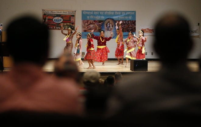 Members of the crowd watch as a group of young ladies perform a dance routine to traditional Hindu music during the 2019 Teej Festival at North High School in Akron.
