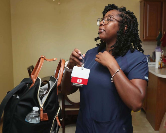 Shavon Hall puts on her Cleveland Clinic RN badge as she prepares to leave for work as an RN at Cleveland Clinic Marymount Hospital Tuesday, Sept. 7, 2021 in Garfield Heights, Ohio. Hall waited four months for the Ohio Nursing Board to process her license.