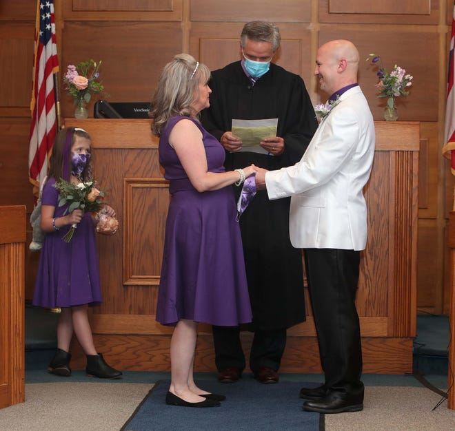 """Barberton Municipal Court Judge Todd McKenney officiates the wedding ceremony of Barberton Councilman Thomas """"Bebe"""" Heitic to Robin Hodgson as Hodgson's daughter Holly Hodgson, 7, watches in the council chambers."""
