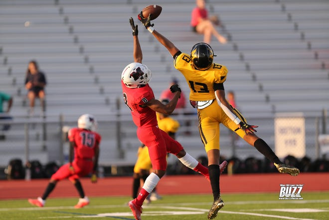 Frisco Memorial's Jaxson Davis (#13) makes a spectacular 1 hand catch for a touchdown even though he was well defended by Jason Fields (#8) of the Melissa Cardinals at Kaykundall Stadium in Frisco, Texas on Sept 3rd, 2021.
