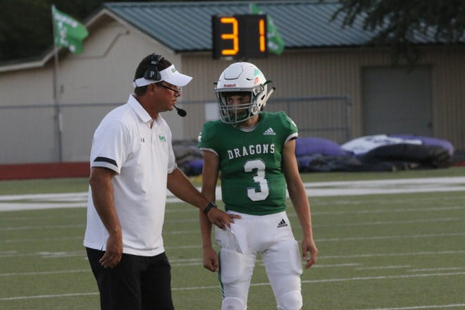 Bangs head football coach and athletic director Kyle Maxfield talks with sophomore Dragons quarterback Kade Minshew as the Dragons offense prepare to run a play Friday night against Florence.