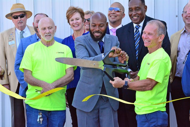 Reentry Opportunity Center Program Director Markus Thomas-Brown, center, and In2Action Director Dan Hanneken cut the ribbon for the center Tuesday morning at 2108 Paris Road. Known as The ROC, it is a recovery community center for those recently released from prison.