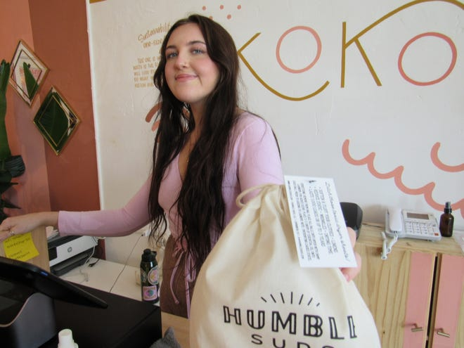 Chloe Lenox, a store associate of Koko, holds up a bag of Humboldt Suds at the Koko store in Columbus' Hilltop neighborhood. Koko, which is all about sustainable soaps, shampoo and other environmentally safe home goods, scheduled a Sept. 11 opening at 3023 Indianola Ave. in Clintonville.