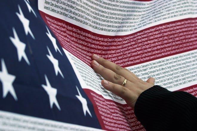 Renata Macedo from Brazil, studying in New York in 2003, runs her fingers over an American flag with the names of all the people who died at the World Trade Center during the attacks on 9/11. Macedo was looking for the name of her friend during the second anniversary of the 9/11 attacks.