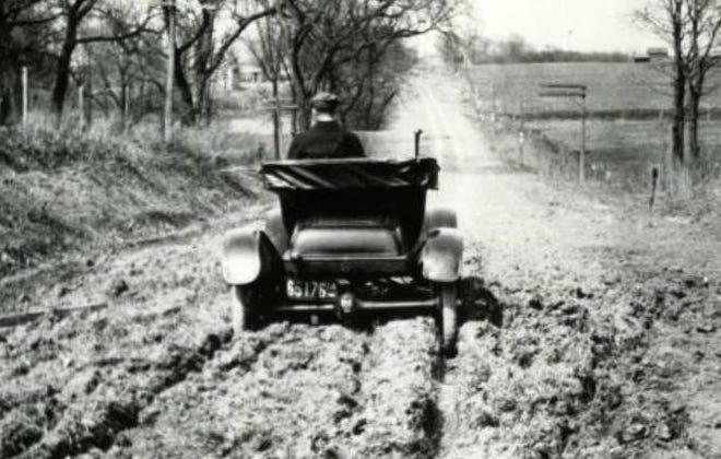 An early auto on an early road – stuck in the mud.