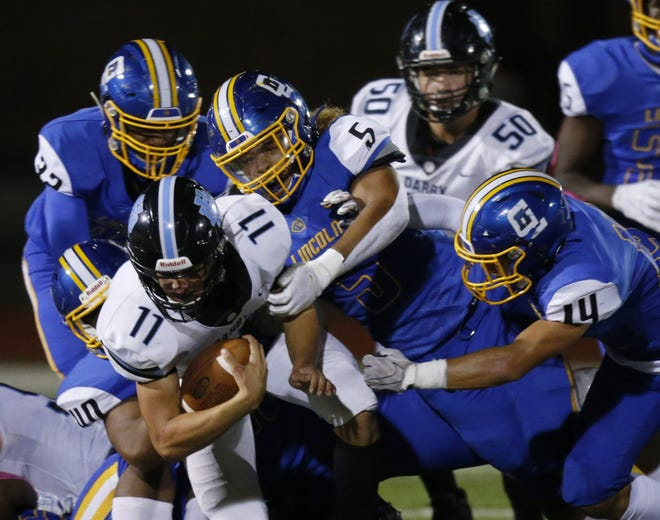 Gahanna's Jabez Hill (32), Kamari Burns (40), Jaden Yates (5) and Kane Baker (14) stop Hilliard Darby quarterback Blake Horvath during a Division I playoff game last season. The Lions will try to avenge their loss in a rematch Sept. 17.