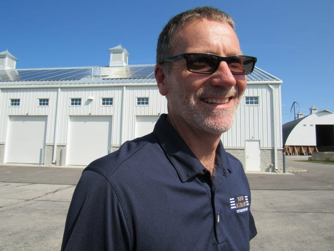 Mark Nemec, public-services director for the city of New Albany, stands in front of the Pubic Service Department building, where workers are installing 271 solar panels on the part of the roof facing south. The shiny panels are visible on the roof. The $230,000 project is expected to be completed by the end of September.