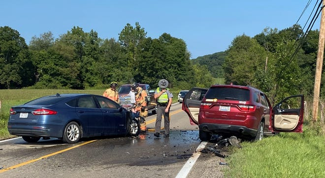 Cambridge firefighters extinguish hot spots in a Ford Fusion that caught fire following a head-on collision Tuesday morning on Bloomfield Road (Ohio 209) north of Cambridge. Three motorists were transported to the hospital with injuries. Trooper Keith Roe of the State Highway Patrol's Cambridge post conducted the crash investigation.