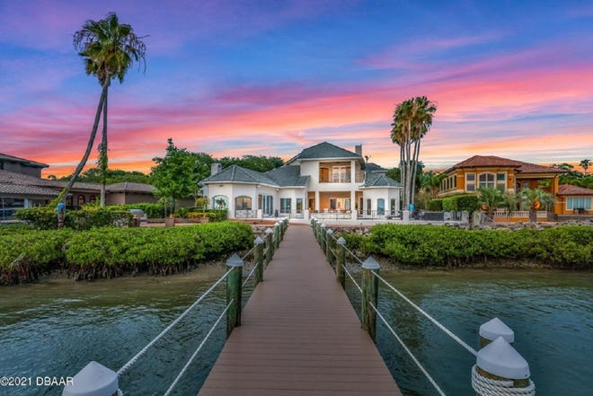 Equipped to entertain, the outdoor living space of this boat lover's dream in Ponce Inlet offers large decking, a summer kitchen, a generous pool, with a waterfall, and the deep-water dock.