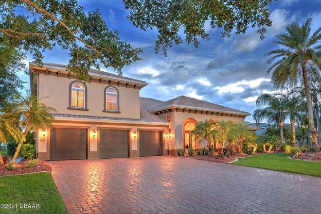A beautiful and expansive paver driveway leads up to This stunning Johnson Group-built waterfront estate in Ormond Beach.