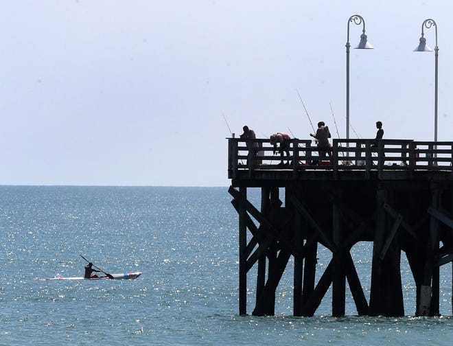 A kayaker paddles past the fishermen on the end of the Daytona Pier, Tuesday, Sept. 7, 2021.