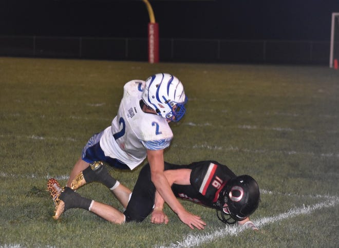 Orion defensive back Jared Mohr, right, upends the ballcarrier, Princeton quarterback Teegan Davis, short of a first down near midfield in the fourth quarter on Friday, Sept. 3, at Charger Field.