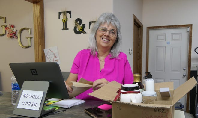 Ruby Yoder, the owner of Yoder Treasures & Treats, packs up a customer's order at her Main Street store in downtown Yoder.