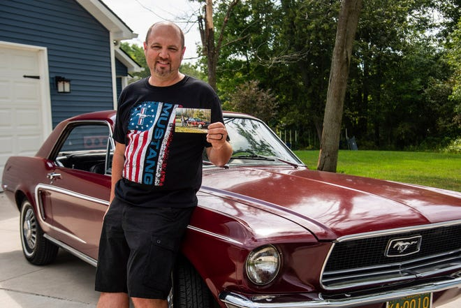 Jeff Penrod holds a picture of himself at age 14 while standing next to his 1968 Ford Mustang Wednesday, Aug. 18, 2021, at his home in Swartz Creek, Mich. When his father sold the vehicle because Penrod failed to keep straight A's in school, Penrod kept a key to the car.  His wife, Brianna, bought the same car 23 years later as a Father's Day gift for Penrod. (Isaac Ritchey/The Flint Journal via AP)