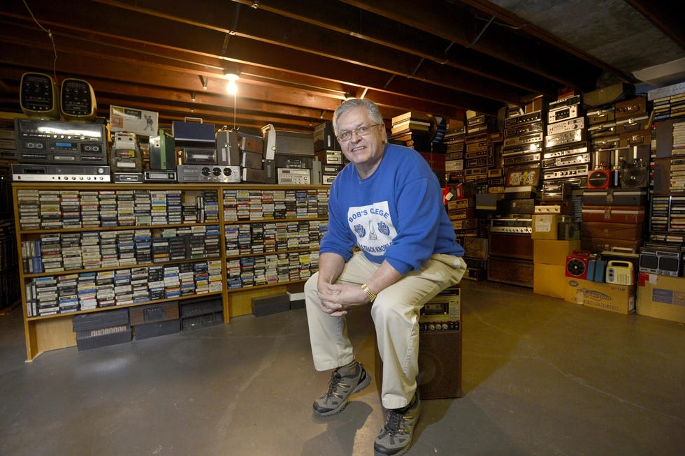 In this 2013 photo, Bob Hiemenz rests on an eight-track karaoke machine in the basement of his Peoria home. Behind him are many of the selections from his world's-largest collection of eight-track tapes, now numbering almost 100,000. Hiemenz, who now lives in Quincy, is taking offers on the collection, which includes more than 700 eight-track players.