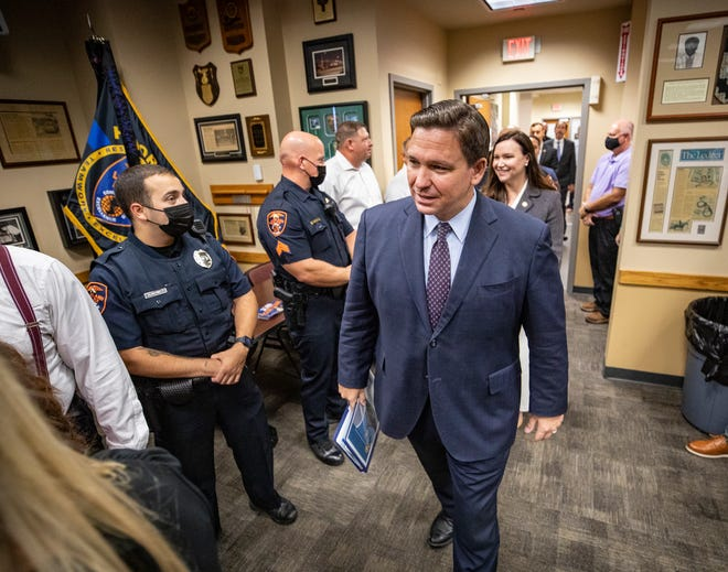 Florida Governor Ron DeSantis followed by Florida Attorney General Ashley Moody visits the Lakeland Police Department to announce a hiring bonus for new Florida police officers at the Lakeland Police department in Lakeland  Fl. Tuesday Sept. 7 2021. Lakeland Police Chief Ruben Garcia did not attend as he was at home recovering from Covid -19 infection. ERNST PETERS/ THE LEDGER