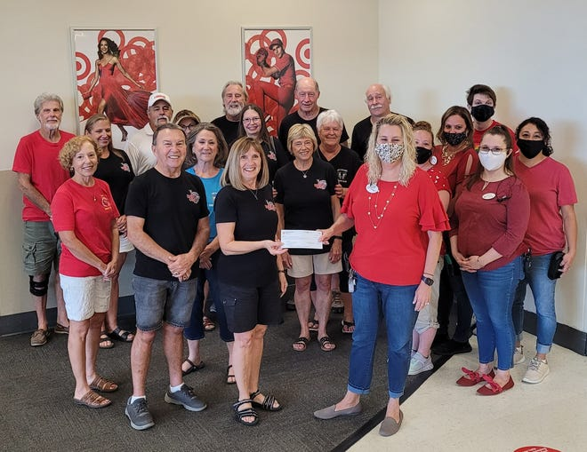 Danna Hiner and other Idiots Club volunteers accept the Target Circle donation from Kim Kirkendoll, store director, and other store associates.