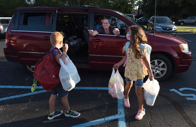 Megan and Mike McWilliams say goodbye to their children as they drop them off at Arborwood Elementary School's North Campus Tuesday morning, which was the first day of school for Monroe Public Schools. MacKenzie, 7, is a second grader. Marshall, 5, is in Kindergarten.