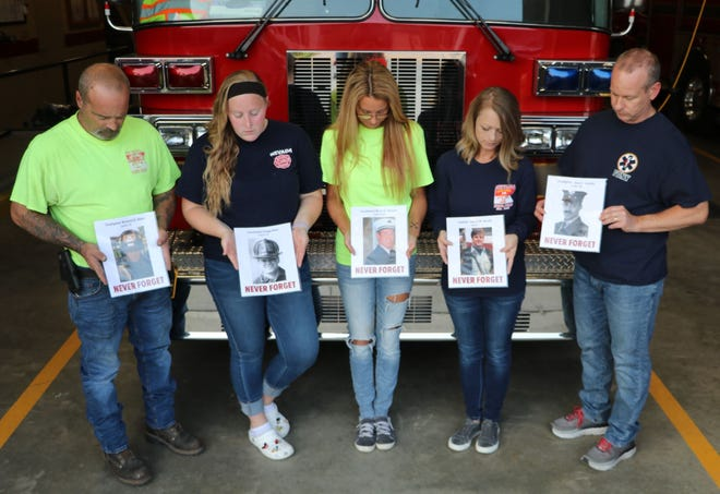Members of the Nevada Fire Department hold a few of the photos of the 343 firefighters who were killed in the 9/11 tragedy. The public is invited to take part in two vigils on Saturday, Sept. 11, at the Nevada Fire Station. Both vigils will pay tribute to those who were lost 20 years ago.
