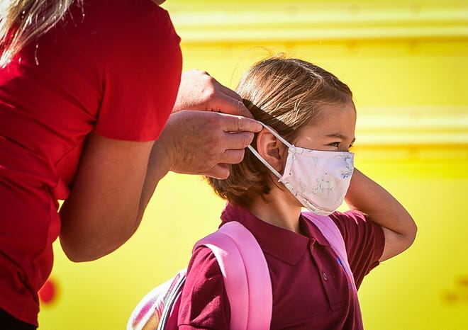 A mother helps her daughter put on a facemask before entering the building at Utica Academy of Science Elementary School on Tuesday, September 7, 2021.