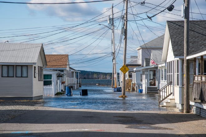 Increased sea level rise leaves roads in a section of Hampton, N.H. underwater during a king tide.