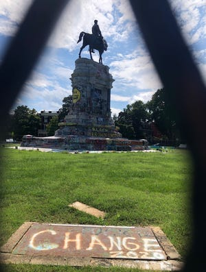 The statue of Robert E. Lee, located in a traffic circle at the intersection of Monument and Allen avenues in Richmond, is photographed from behind temporary fencing around the perimeter of the traffic circle Monday, Sept. 6, 2021.