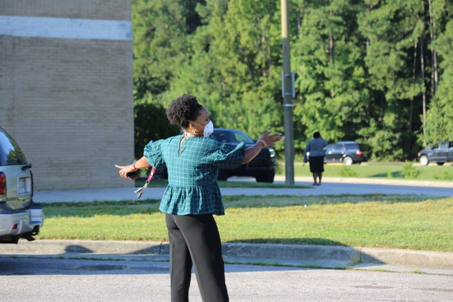 A teacher directs traffic at the Vernon Johns Middle School drop-off on the First Day of School.