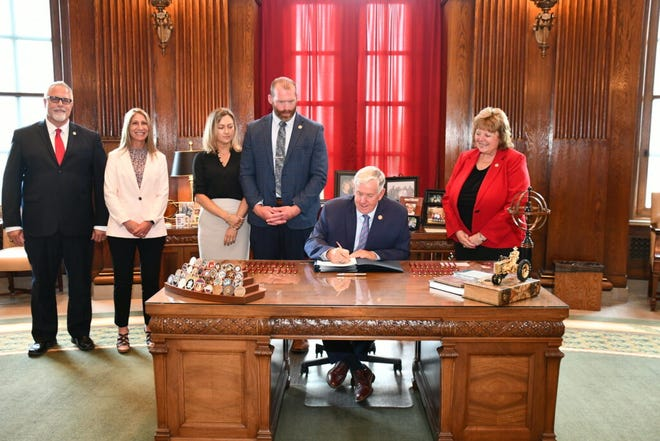 Flanked by state lawmakers, Gov. Mike Parson signs House Bill 604 into law on July 7, 2021 (photo courtesy of Missouri Governor's Office).