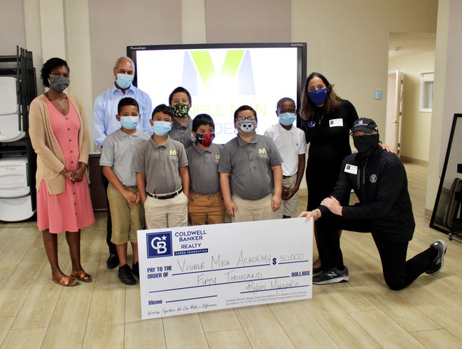 Representatives of Coldwell Banker Realty CARES present a $50,000 check to staff and students at Visible Men Academy, in Bradenton.