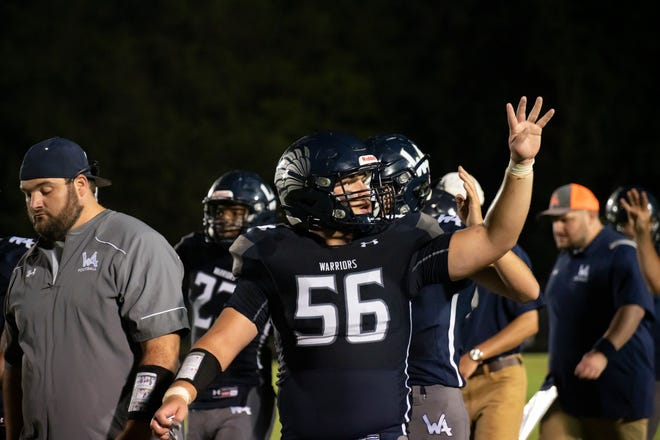 """Western Alamance High School senior Justin Lambert holds up """"4"""" as the team walks off the field at halftime during their lopsided loss against Northern Guilford on Friday night in Elon, NC on September 3, 2021."""