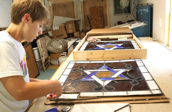 Stained glass artist Sarah Siepler works on repairing a stained glass window from Bedford Furniture Galleries.