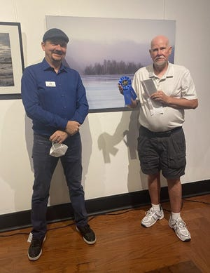 """From left, Jayson Kretzer, executive director of the Panama City Center for the Arts, poses with Chris Calohan, winner of Best of Show for his photograph titled """"Island in the Mist,"""" at Panama City Center for the Arts on Sept. 3."""
