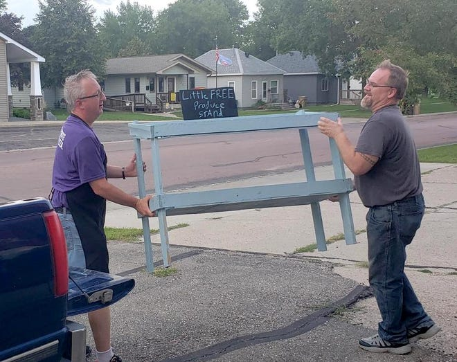 """Wise Pizza employee Lance Rambow, left, and Lee Bruns unload the new """"Little Free Produce Stand."""""""