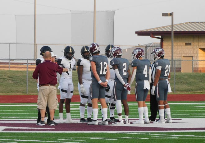 Ennis team captains Jackson Gilkey (12), Dee Johnson (2), Jace Berry (4) and Eric Gonzalez (21) line up for the coin toss before Friday night's game against Keller Fossil Ridge. The Lions won, 36-29.