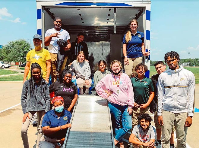 Life High School Waxahachie students help load a moving truck with more than 160 cases of bottled water to aid victims of Hurricane Ida.