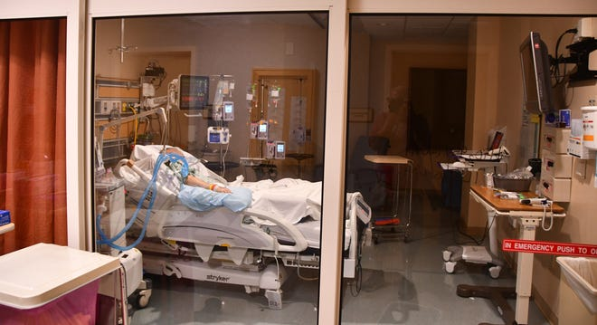 A COVID-19 patient lies in a closed room in the ICU at Parrish Medical Center.
