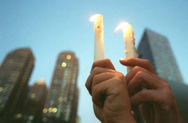 Text: Robert Garmet, right, and his son Eric Garmet, 10, hold candles side-by-side in a twin tower representation at a vigil for victims of the terrorist attacks at Union Square in New York on Sept.14, 2001. (AP Photo/Western Kentucky University, Jonathan Miano)