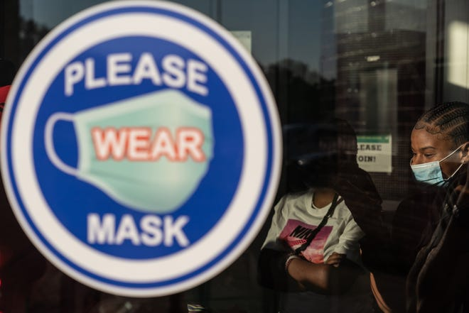 Signage for the use of a mask is posted at the entry as Ecorse High School students enter the school during the first day at Ecorse High School in Ecorse on September 7, 2021.