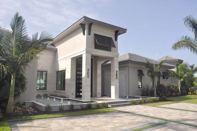 This new home in Quail West by Florida Lifestyle Homes is known as the Waterfall House because of the fountains and waterfalls on either side of the entrance.